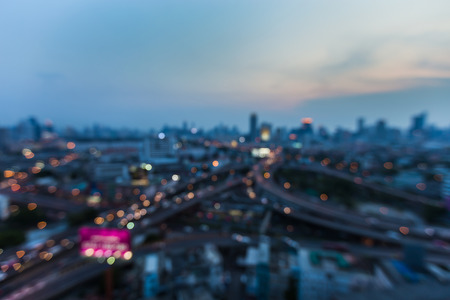 Night aerial view, blurred bokeh light city and overpass highway intersection, abstract background
