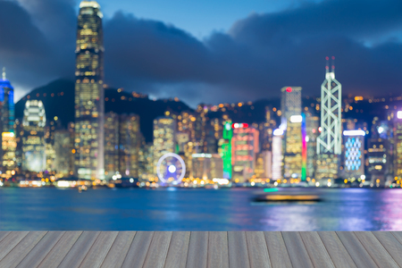 Opening wooden floor, Night blurred bokeh light Hong Kong city business downtown seafront, abstract backgorund Stock Photo