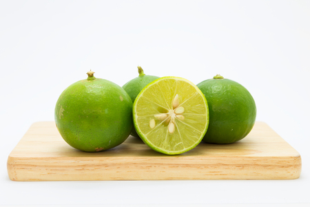 Wooden board with fresh limes on white background