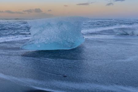 Ice braking on black sand beack seacoast skyline, Iceland winter season natural landscape background