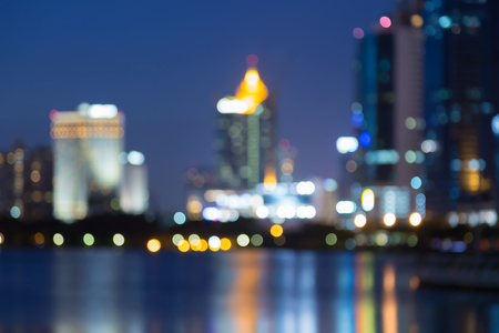 Night light blurred bokeh city office building water front, abstract background