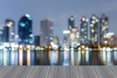 Opening wooden floor, Twilight blurred bokeh light office building downtown, abstract background Stock Photo