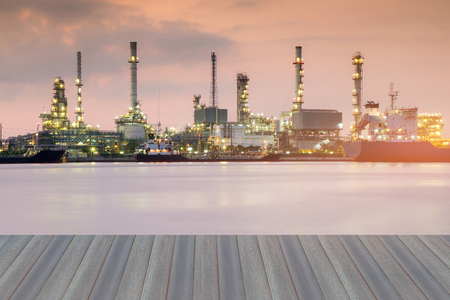 Opening wooden floor, Oil refinery river front at twilight Stock Photo