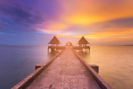 Beauty of sunset seacoast skyline with walkway to abandon temple in ocean, natural landscape background