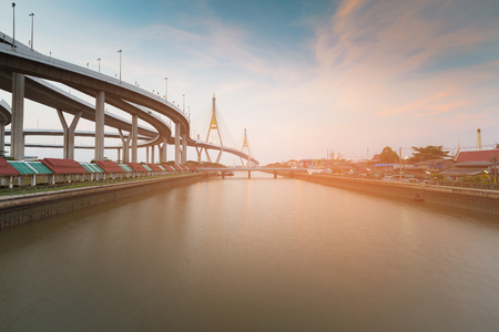 Bangkok River with twin suspension bridge and highway background, Thailand Stock Photo