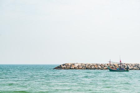 Small fishing ship on seacoast, natural landscape skyline background