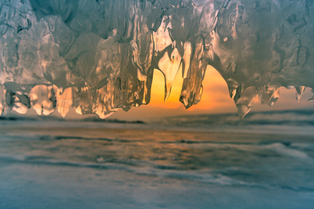 Ice cave with sunset sky background close up, winter season natural landscape