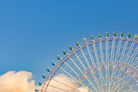 Big ferris wheel against blue sky in amusement park