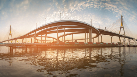 Panorama sunset over suspension bridge connect to intersection highway river front Banco de Imagens