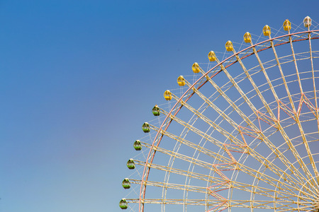 Funfair amusement path of giant ferris wheel with clear blue sky background