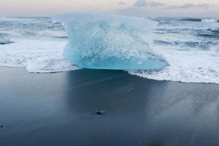 Iceberg on black sand beach over Jokulsarlon diamond beach, winter season Iceland natural landscape Reklamní fotografie