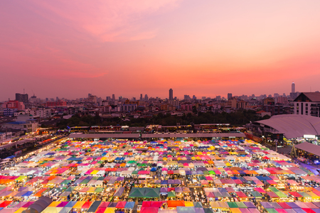 Dramatic sunset sky over night flea market aerial view