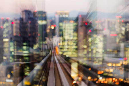Moving train track into city blur light central business downtown, abstract background