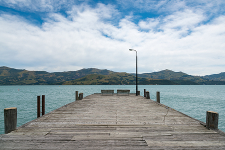 Wooden pier leading to water lake, New Zealand natural landscape background