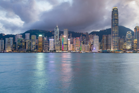 Night Hong Kong central business downtown with seacoast front, cityscape background