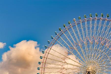 Amusement park ferris wheel against blue sky background