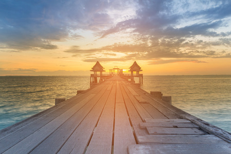 Wooden walking path leading to sunset seacoast skyline, natural landscape background