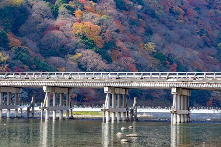 Arashiyama wooden bridge cross over river and autumn season change background, Japan
