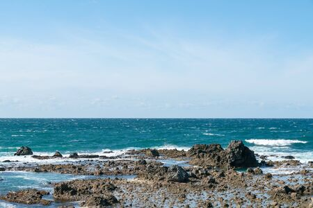 Sea and blue skyline with rock beach, natural landscape background