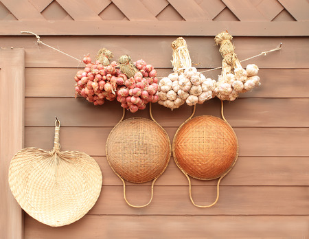 Onion and garlic hung on the wall in kitchen thailand style photo