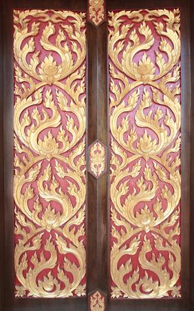 Ancient golden carving wooden door of Thai temple. Thailand photo