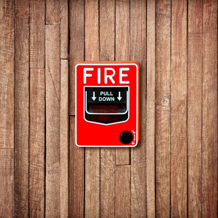 Fire break glass switch on  wooden wall background photo