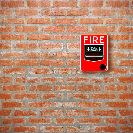 activate: fire break glass alarm switch on brick wall background