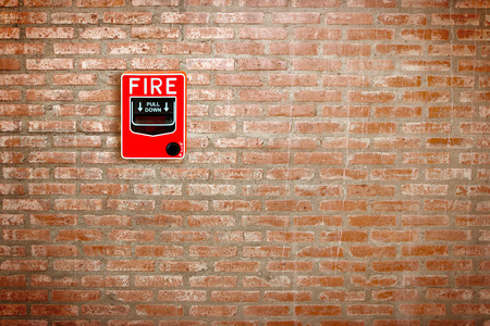 fire break glass alarm switch on brick wall background photo