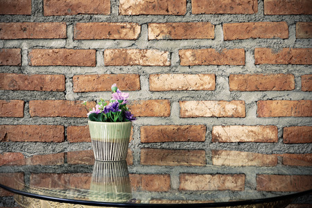 Flower pot on the table with glass brick wall background. photo