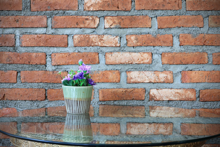 glass brick: Flower pot on the table with glass brick wall background. Archivio Fotografico