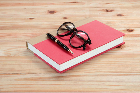 actuality: red book with glasses and pen on the wooden Stock Photo