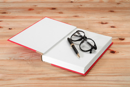 untidiness: red book with glasses and pen on the wooden Stock Photo