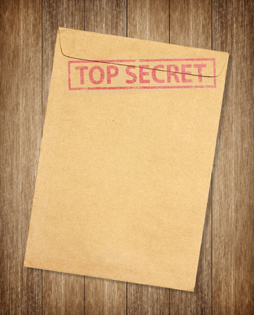 Brown envelope with top secret stamp isolated on on wood background