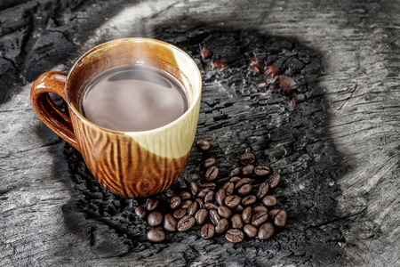 cinder: Cup of coffee with coffee beans on a wood cinder Stock Photo
