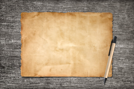 table scraps: old brown paper and pen on wood background for texture Stock Photo