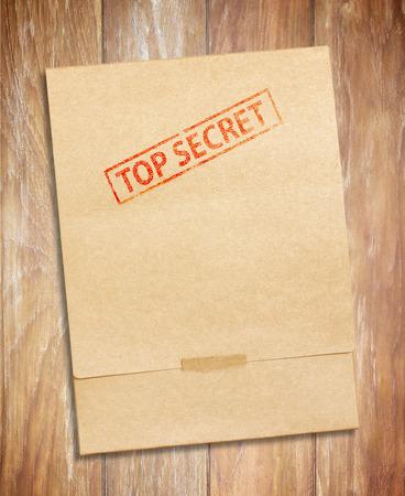 envelop met top geheime stempel en papieren, op houten tafel Stockfoto