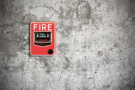 sprinkler alarm: fire break glass on the concrete wall background Stock Photo
