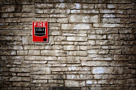 sprinkler alarm: fire break glass fire alarm on old grunge wall Stock Photo