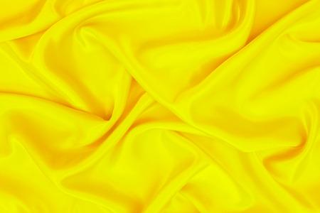 abstracte achtergrond gele luxe doek of golvende plooien van grunge zijde textuur materiaal