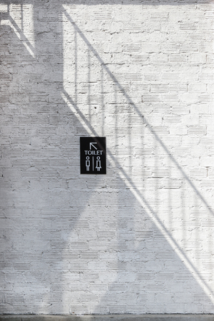 Light and shadow of stairway on the white wall with toilet sign to toilet area.