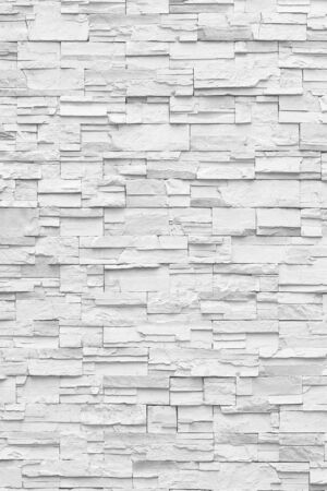 Superficie de pared blanca de pared de piedra en tonos grises para usar como fondo.