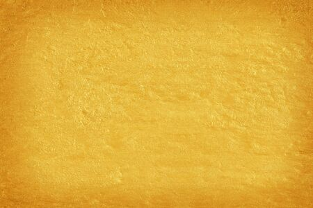 Gold paint on cement wall texture.