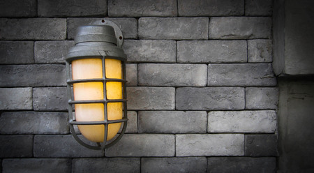 antique furniture: grung black brick wall with lamp On the street.can be used as background