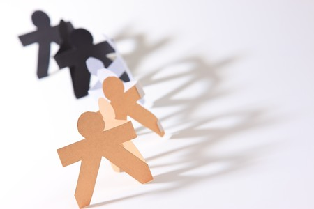 Paper cut into people hold their hands connected show human race equality on white background  版權商用圖片