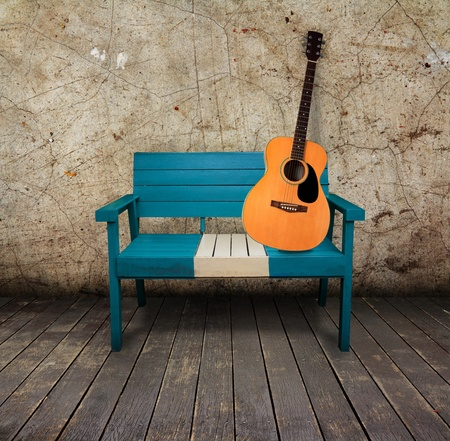 Green chair and acoustic quitar in a grunge room with wooden floor Imagens
