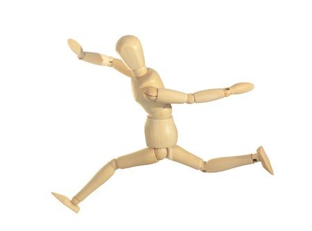 wood figurine: Maniqu� de madera amarilla en la acci�n de ejecuci�n salto aislados sobre fondo blanco Foto de archivo