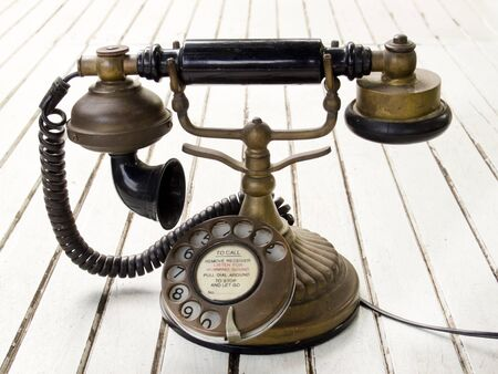 Dirty old classic retro style analog telephone on white desk
