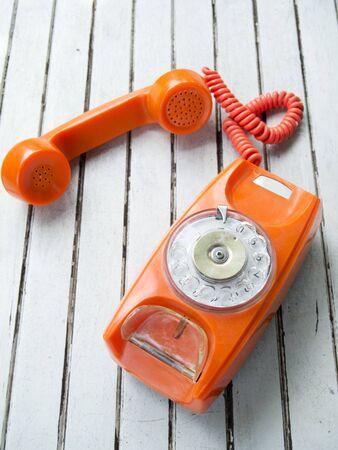 Dirty old orange dial telephone photo