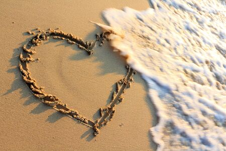 Water splash on heart shape draw on beach photo