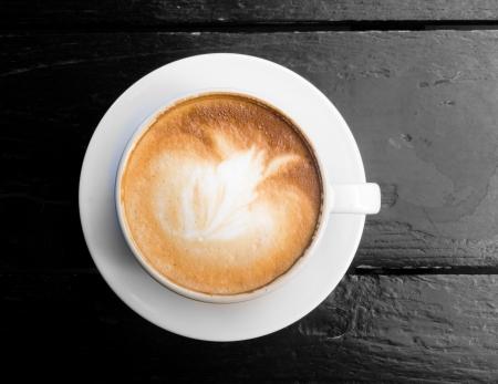 trompo de madera: Blanco taza de caf� caliente con leche en la mesa de madera oscura